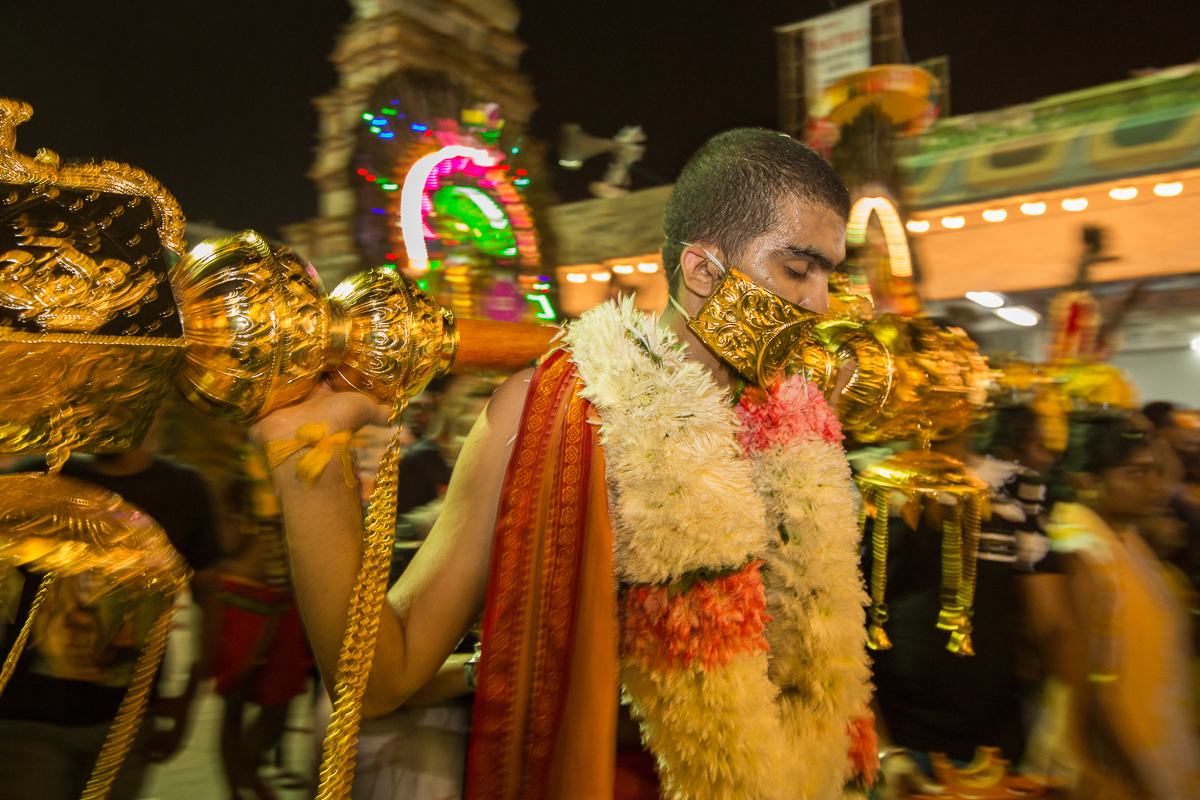 Manpreet carries a decorated wooden club as a self penitence act during his Thaipusam pilgrimage. His fourth time at Thaipusam, he came from Singapore to join the festival with family and friends seeking good health and prosperity. [Alexandra Radu/Al Jazeera]