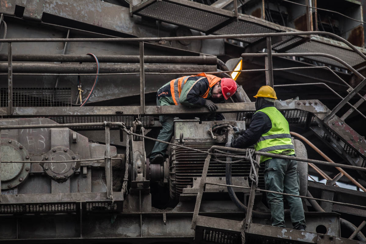 Two  workers operate a coal excavator in Ptolemaida. [Anna Pantelia/Al Jazeera]