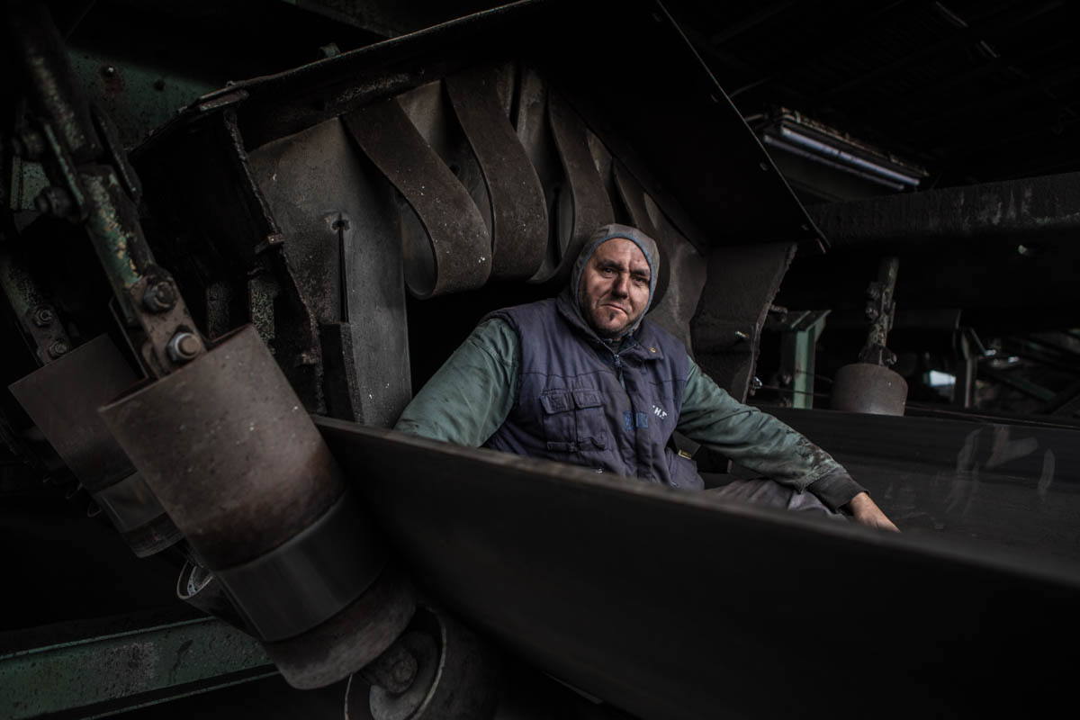 Giannis, a PPC worker, poses after finishing his work near the conveyor belt that transfers coal to the production unit. Accidents are common and sometimes fatal. Safety measures are often not followed. Since 1970 more than 106 people have died in work-place accidents. [Anna Pantelia/Al Jazeera]