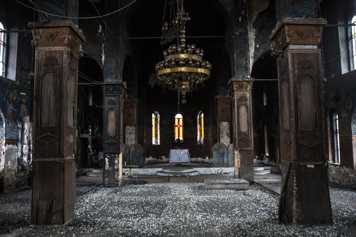A church lies abandoned in the middle of the coal mine. It's all that remains of Charavgi, a village that was expropriated and its inhabitants removed so that the mines could be extended. [Anna Pantelia/Al Jazeera]
