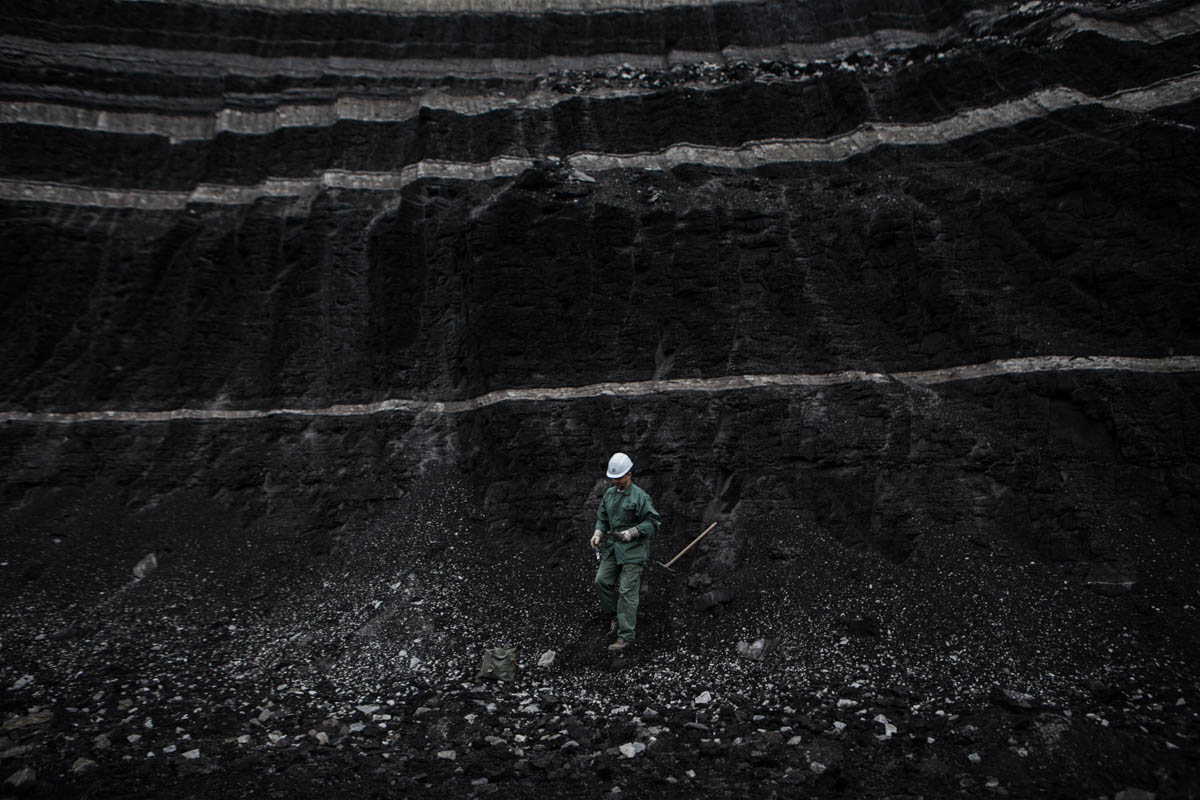 A PPC worker collects a coal sample for examination. [Anna Pantelia/Al Jazeera]