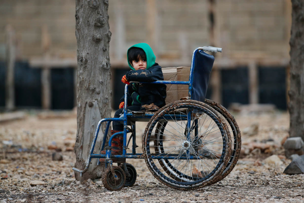 A Syrian child sits on a wheelchair after he and his family crossed into Turkey, in the Oncupinar border crossing with Syria, known as Bab al Salameh in Arabic, in the outskirts of the town of Kilis, Turkey. [Lefteris Pitarakis/AP Photo]