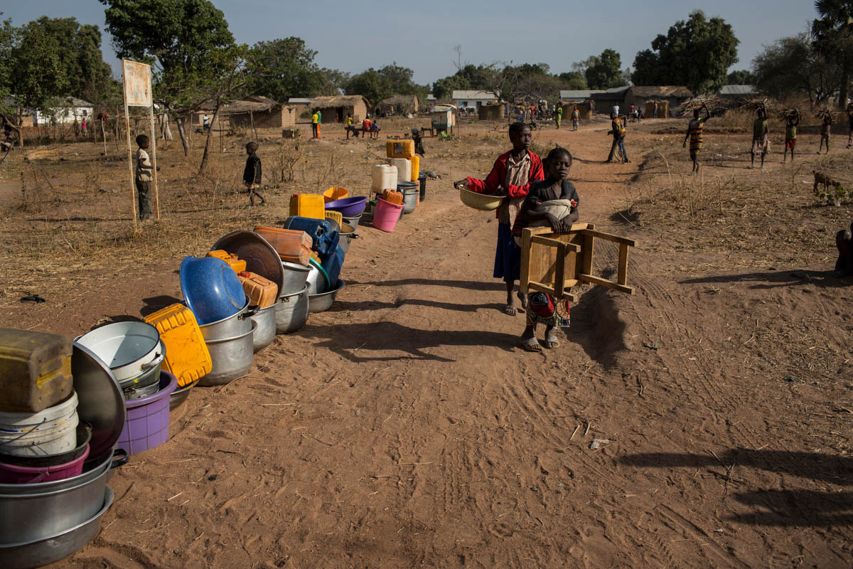 Containers for water are lined up outside a well near the Avenue Church in Paoua. With the influx of some 65,000 IDPs, the population of Paoua has more than doubled making access to clean water a pressing issue. [Will Baxter/ Al Jazeera]