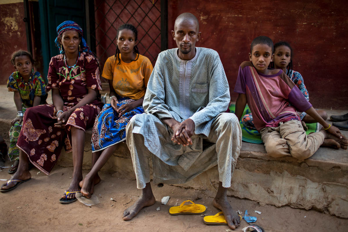 Mepala Bakary (center) sits with several of his family members at the abandoned house where they have taken shelter outside the MINUSCA base in Paoua town. On 24 January, Bakary's 60-year-old father Moderi Machido was pulled from the back of a motorbike, and stoned and beaten to death by a Christian mob. The lynching took place just footsteps away from the local gendarmerie post, and only 100 metres from the Paoua base of MINUSCA. [Will Baxter/ Al Jazeera]