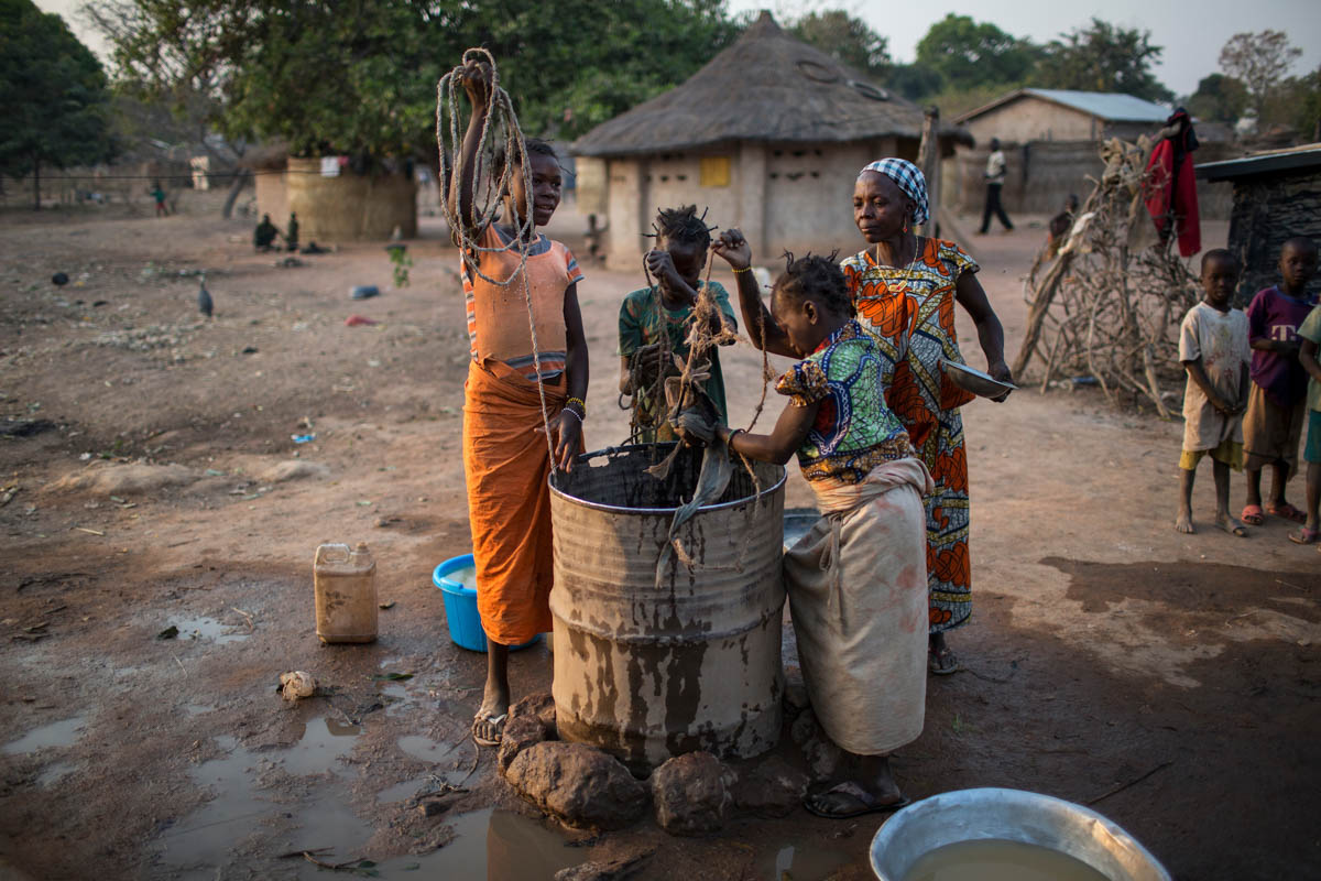 Displaced girls staying with a host family draw water from a well in Paoua. 'The wells were only meant for 40,000 people, the population of Paoua town. But, with 65,000 more people arriving, the resources that were meant for 40,000 will now have to serve a group of about 100,000 people. With this kind of pressure, you're likely to see tensions between the IDPs and the host community,' said Inganji. [Will Baxter/Al Jazeera]
