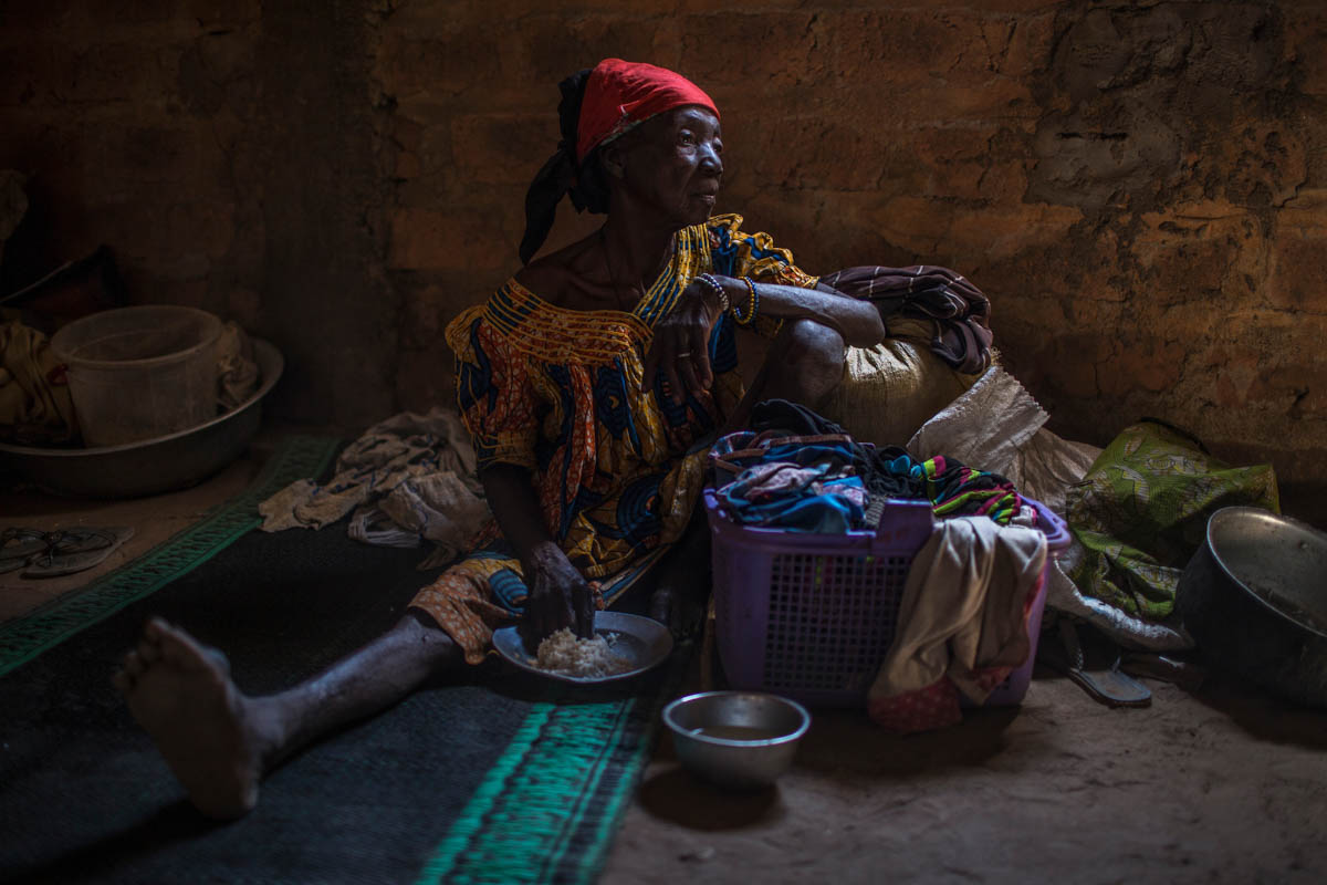 A displaced woman sits with her belongings inside the Saramandja Church, which is hosting IDPs in Paoua. [Will Baxter/ Al Jazeera]