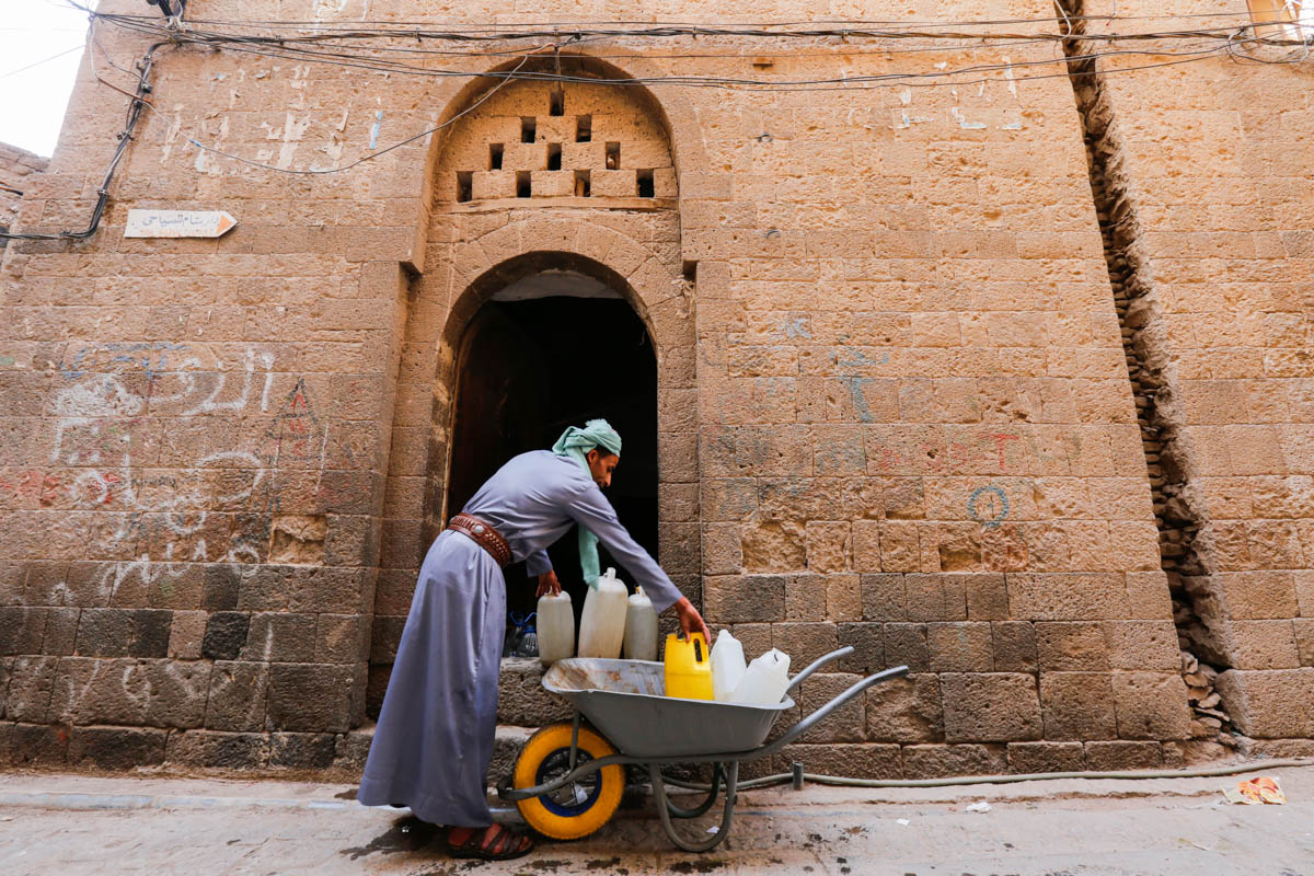 Mohammed Ali unloads jerry cans from his wheelbarrow in the Old City of Sanaa. The 33-year-old fled with 10 family members from Yemen's northern province of Sa'ada, on the border with Saudi Arabia, after his house was destroyed. [Mohammed Hamoud/UNHCR/Al Jazeera]