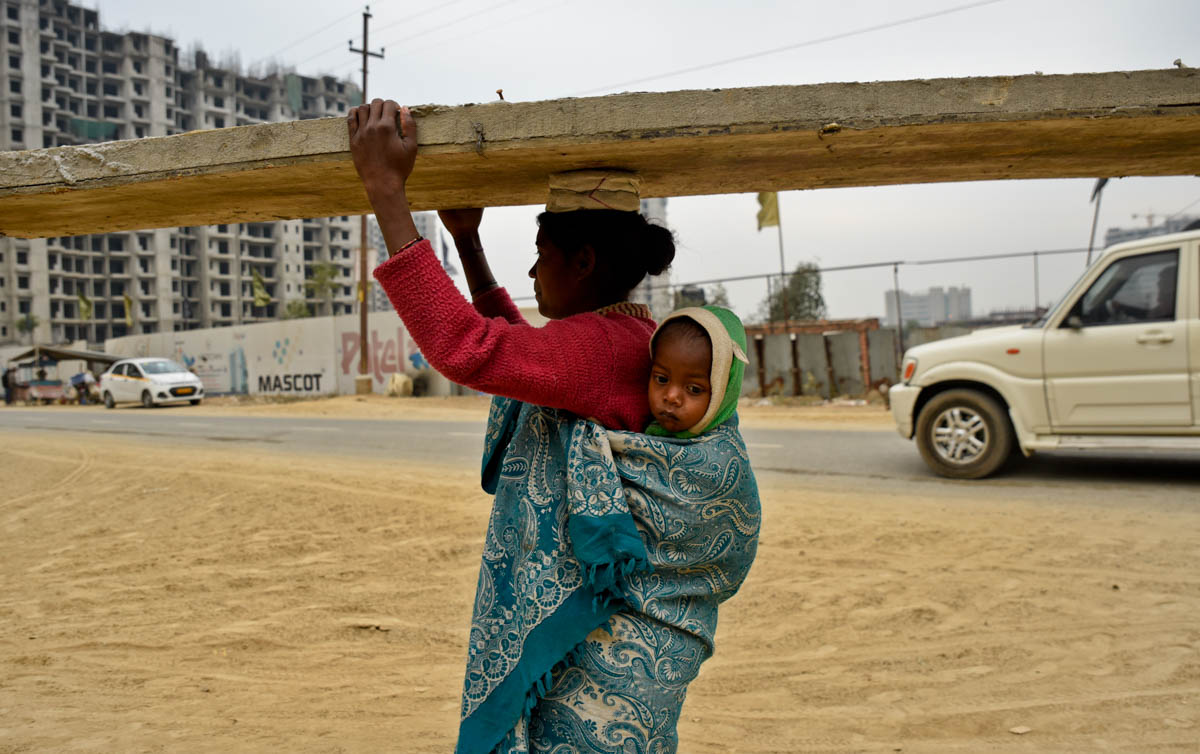 An Indian woman working at a construction site carries her 18-month old child on her back as she works in Greater Noida, India. The mother, one among the many migrant workers from the northern Jharkhand state says she always carries her child to work since she doesn't have the option of leaving him with anyone else. [R S Iyer/AP Photo]