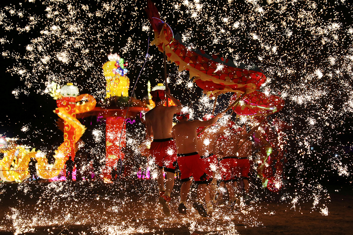 Folk artists perform a fire dragon dance under a shower of sparks from molten iron, ahead of the Chinese Lunar New Year, in Shangqiu, Henan province, China. [Reuters]