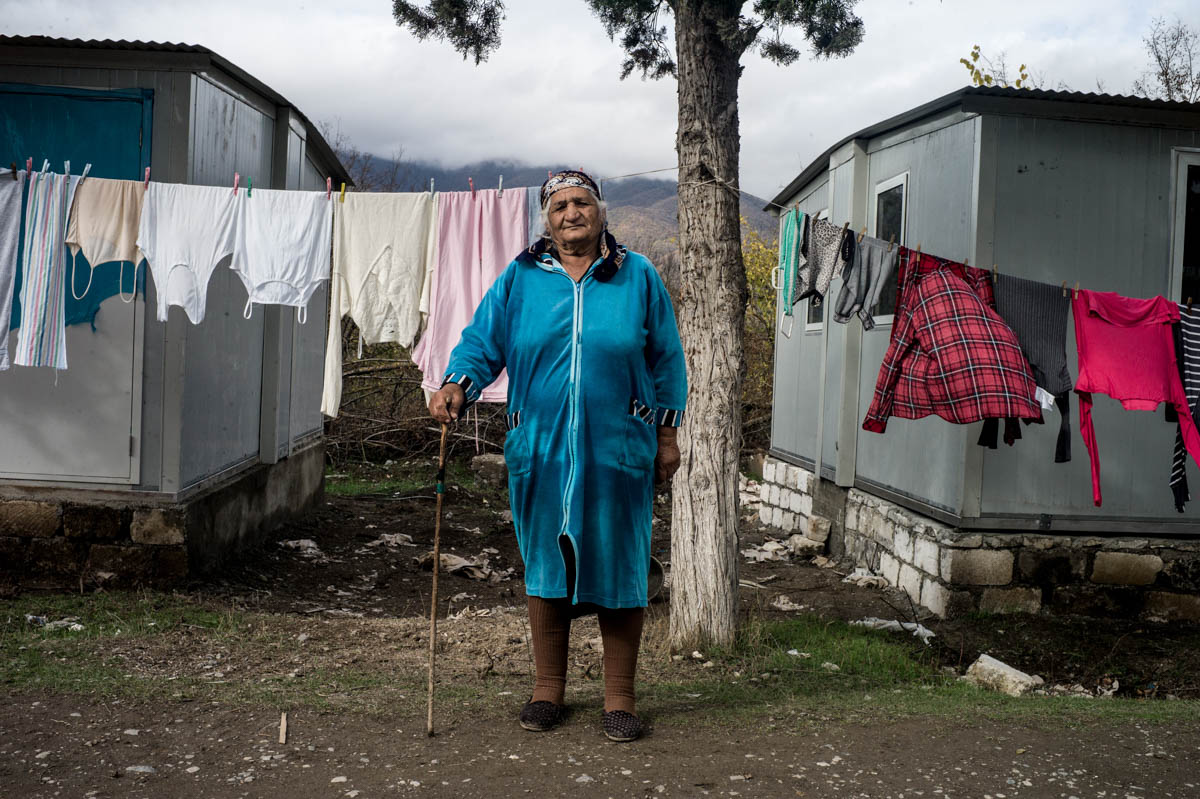 Marusya Babayan stands in front of her temporary accommodation in Alishan village, set up in the grounds of an old military hospital to house the residents of Talish who fled the April 2016 war. [Gus Palmer/Al Jazeera]