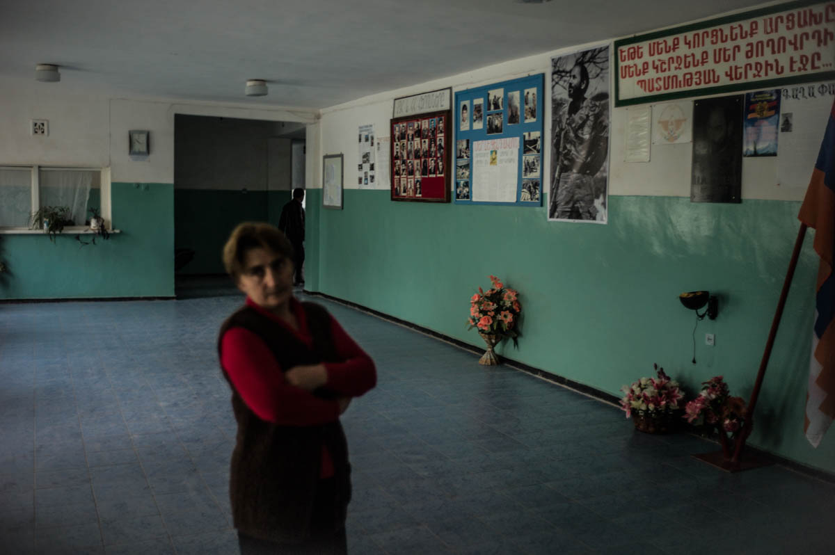 A teacher stands in the entrance of the local school in Berdashen village, Karabakh. Behind her, a wall is dedicated to the portraits of those killed over the past two decades in the war with Azerbaijan. [Gus Palmer/Al Jazeera]