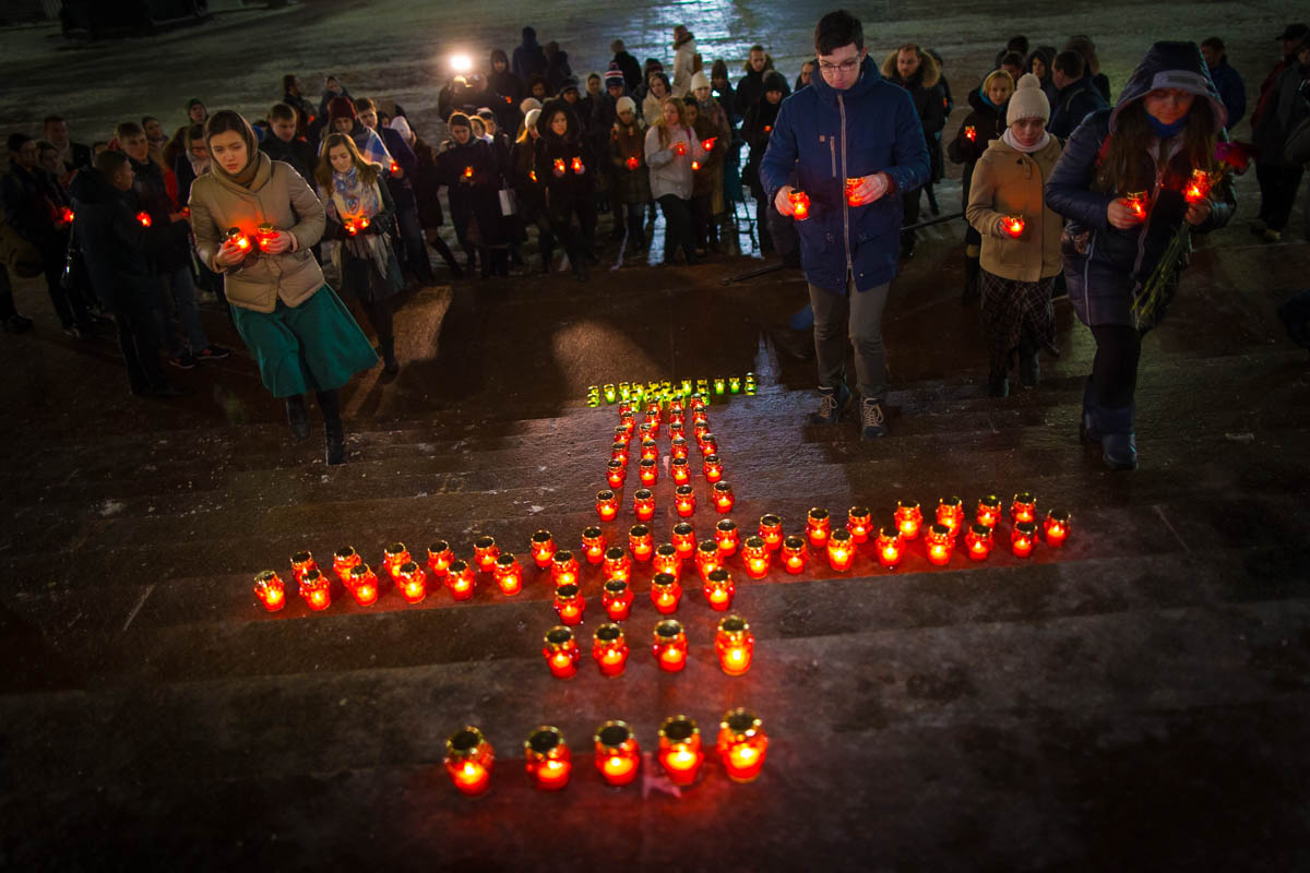 Young people gather at the Cathedral of Christ the Savior in Moscow lighting 71 candles in memory of those killed in the An-148 plane crash. The Russian passenger plane carrying 71 people crashed on Sunday near Moscow, killing everyone aboard. [Alexander Zemlianichenko/AP Photo]