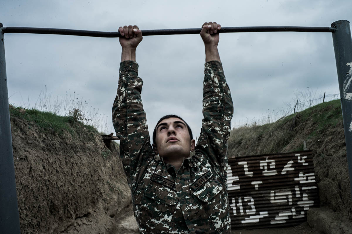 A conscript does pull-ups in a trench at a frontline position. There is little space to move around within the soldiers' barracks, as the positions are closely monitored by the opposite side. [Gus Palmer/Al Jazeera]