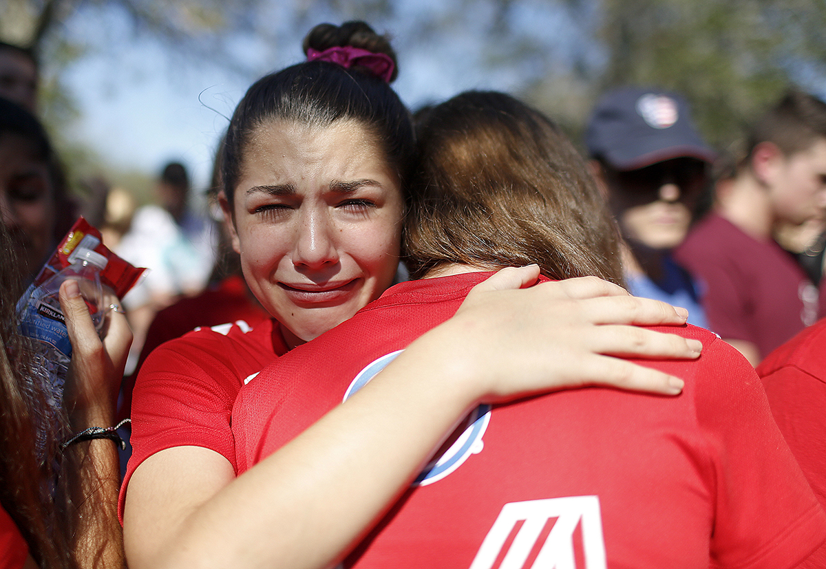 A student mourns the loss of her friend during a community for the victims of the shooting at Marjory Stoneman Douglas High School in Parkland, Florida. Nikolas Cruz, a former student, was charged with 17 counts of premeditated murder on Thursday. [Brynn Anderson/AP Photo]