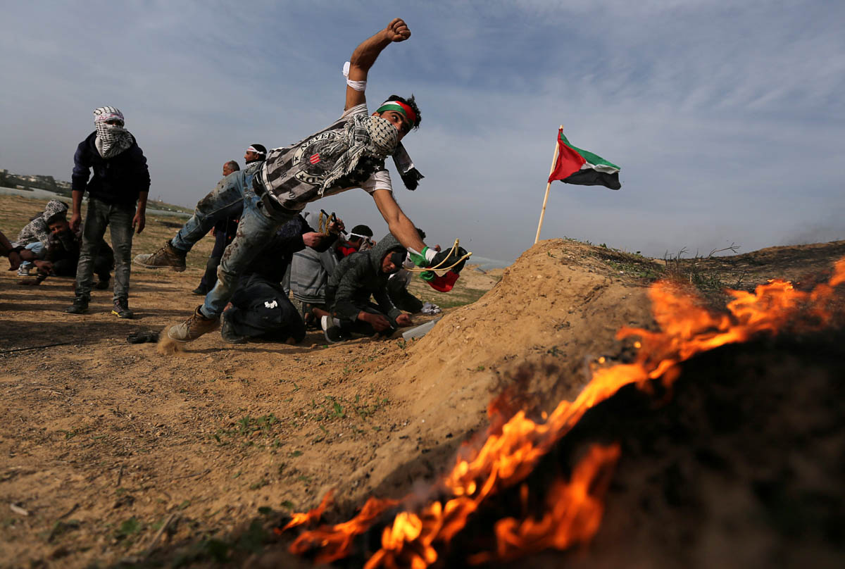 A Palestinian protester reacts during clashes with Israeli forces, near the border with Israel in the southern Gaza Strip. [Ibraheem Abu Mustafa/Reuters]