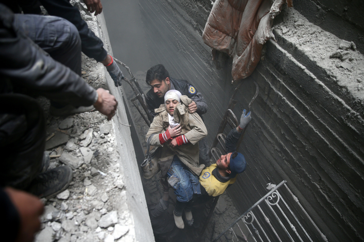 SyriaCivil Defence members help move an unconscious woman from a shelter in the besieged town of Douma, Eastern Ghouta, Syria. [Bassam Khabieh/Reuters]