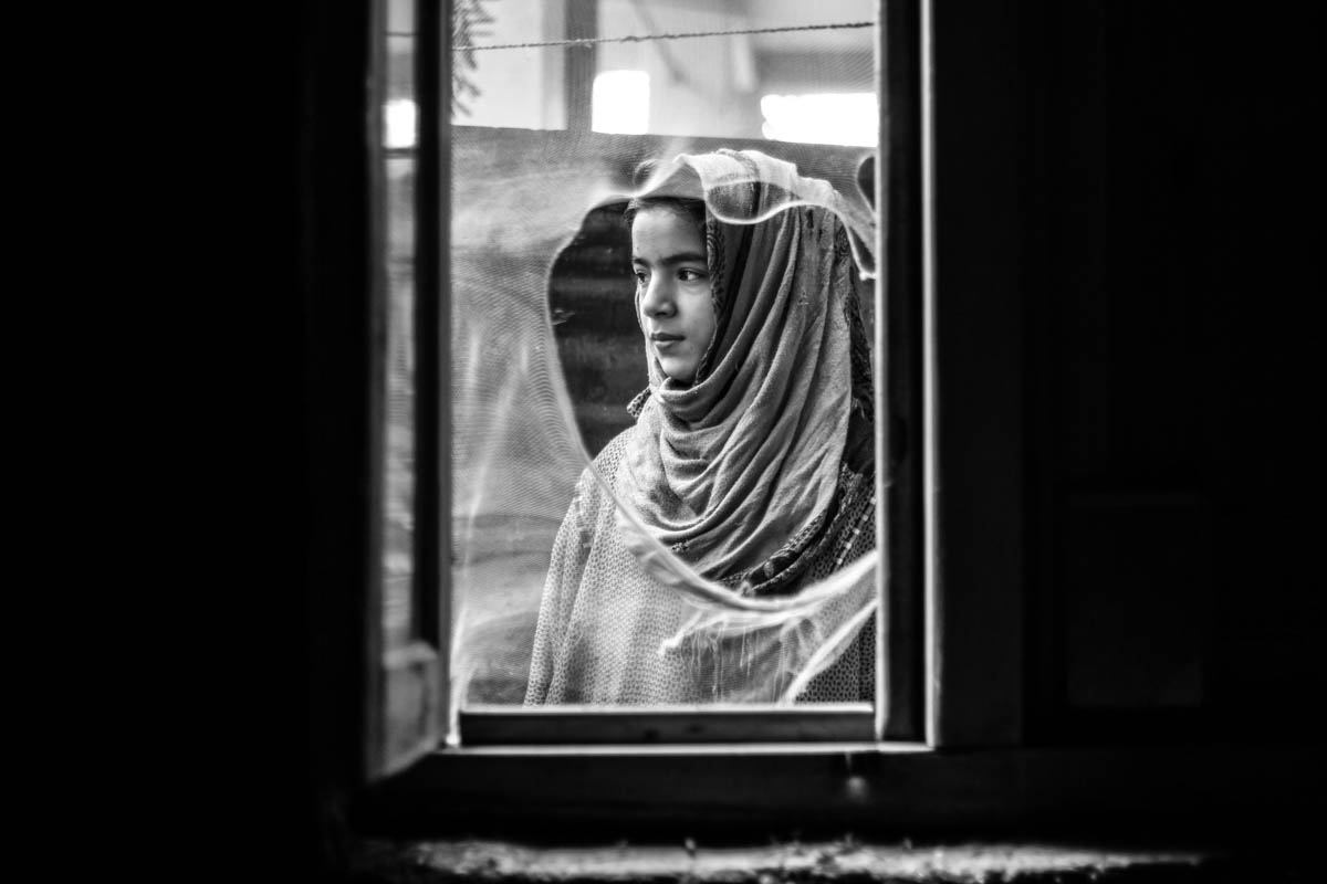 "Ten-year-old Insha looks out of the window of her house in the village of Dialgam in Anantnag district, about 55km south of Srinagar city. Insha's father was killed in a grenade attack in Anantnag town in 2015. ""No one can fill the void left by my father, even though we were poor, he used to take care of all of us,"" Insha says. [Sameer Mushtaq/Al Jazeera]"