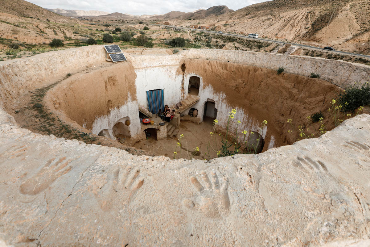 Saliha Mohamedi, 36, sits with her children at their troglodyte house on the outskirts of Matmata. [Zohra Bensemra/Reuters]
