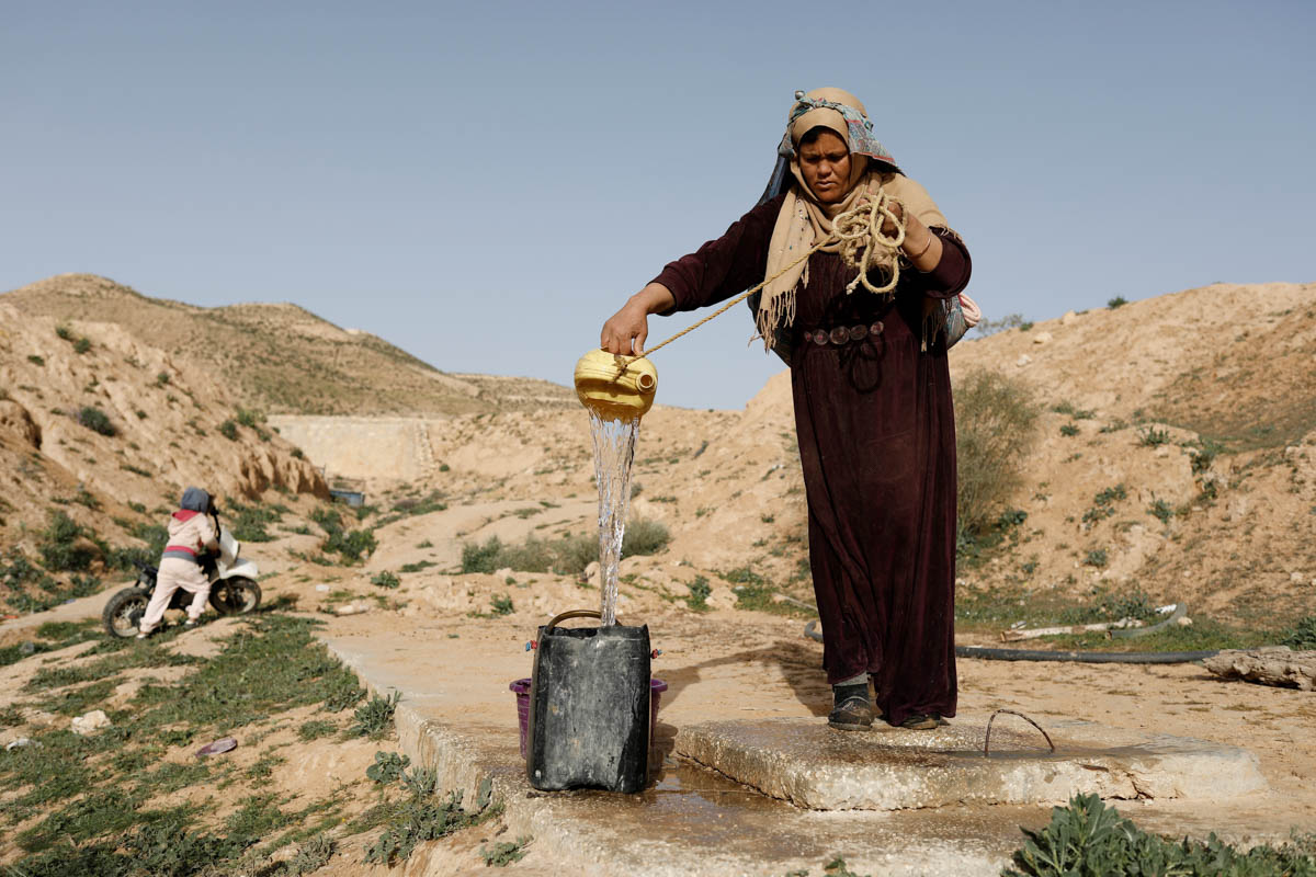"Saliha Mohamedi, 36, fills a bowl from her water storage outside her troglodyte house. ""I don't want to leave my house, it would be as if I was throwing my life and my traditions away,"" Mohamedi said. [Zohra Bensemra/Reuters]"