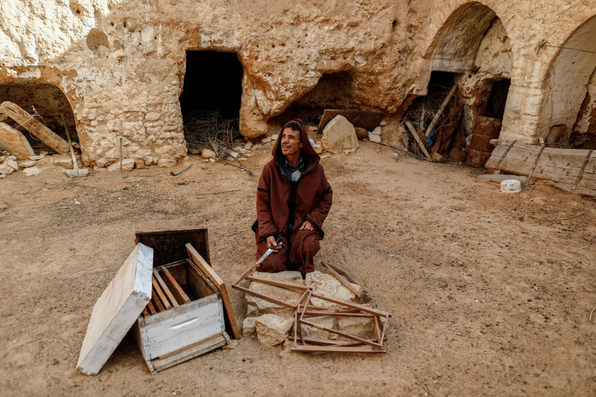 Mustapha, a 54-year-old farmer, sits in the corridor of his family's troglodyte house which was converted into a warehouse. [Zohra Bensemra/Reuters]