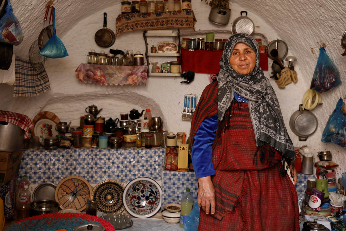 Mounjia, 60, poses for a photograph in the kitchen of her troglodyte house. [Zohra Bensemra/Reuters]