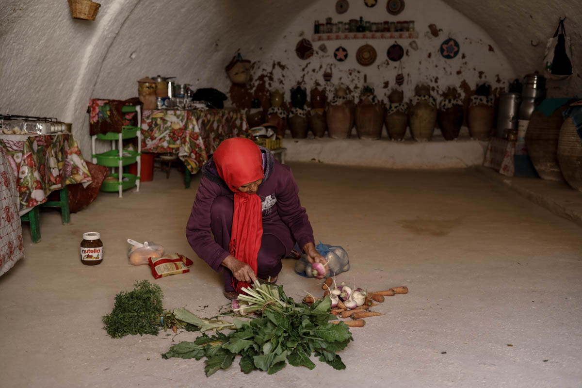 Latifa Ben Yahia, 38, prepares vegetables to cook in the kitchen of her troglodyte house. [Zohra Bensemra/Reuters]
