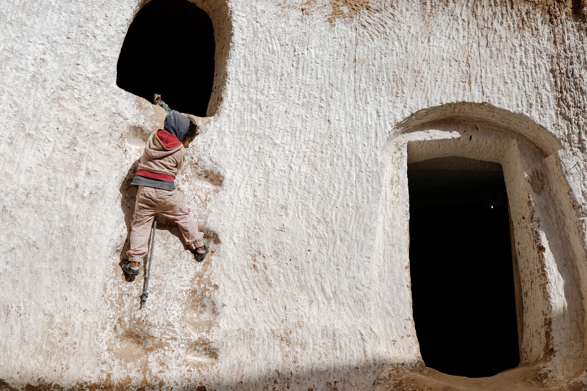 Ahlem, four, climbs up a wall to reach her rabbit's hideaway at her troglodyte house. The homes are concentrated around Matmata, which lies in a cratered landscape dotted with palm trees and olive groves about 227 miles south of Tunis. [Zohra Bensemra/Reuters]