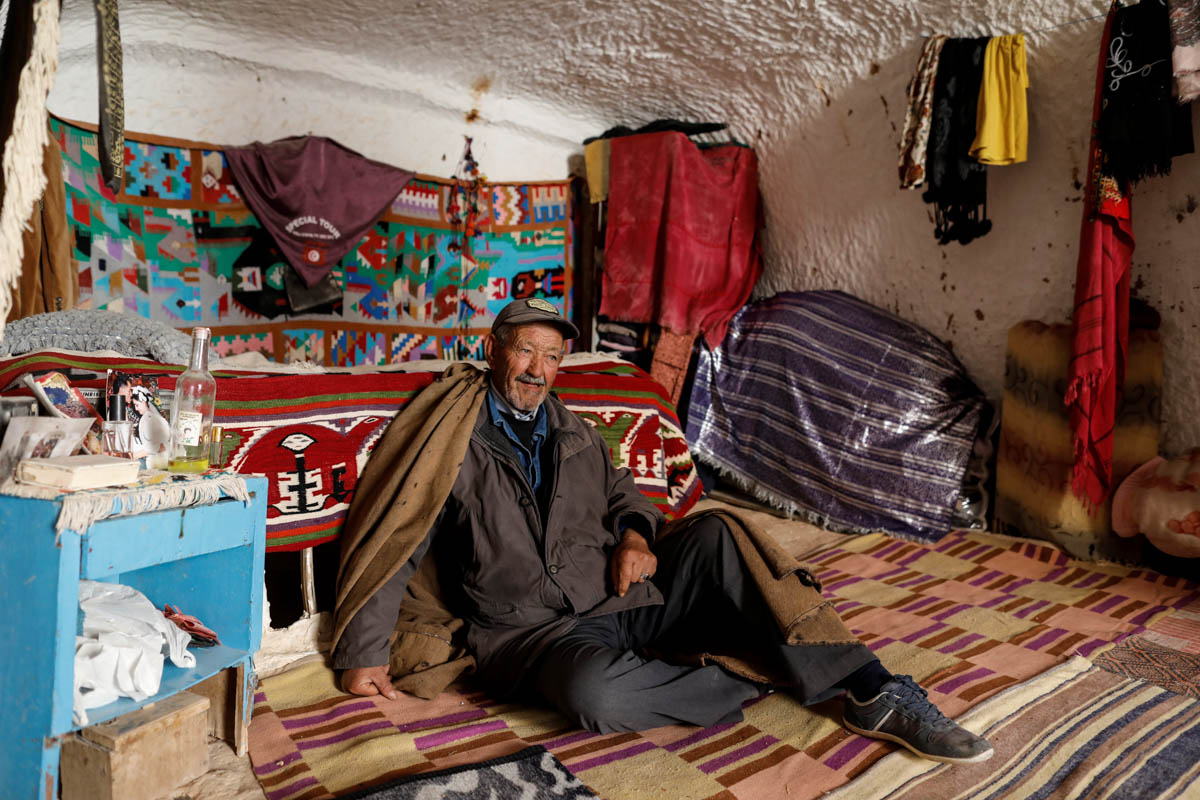"Tayeb, 76, sits inside his troglodyte home in Matmata, Tunisia. ""Our home was open for tourists to visit, but now with the lack of tourists, we don't earn anything. I don't want to leave my house, it's where I grew up,"" Tayeb said. [Zohra Bensemra/Reuters]"