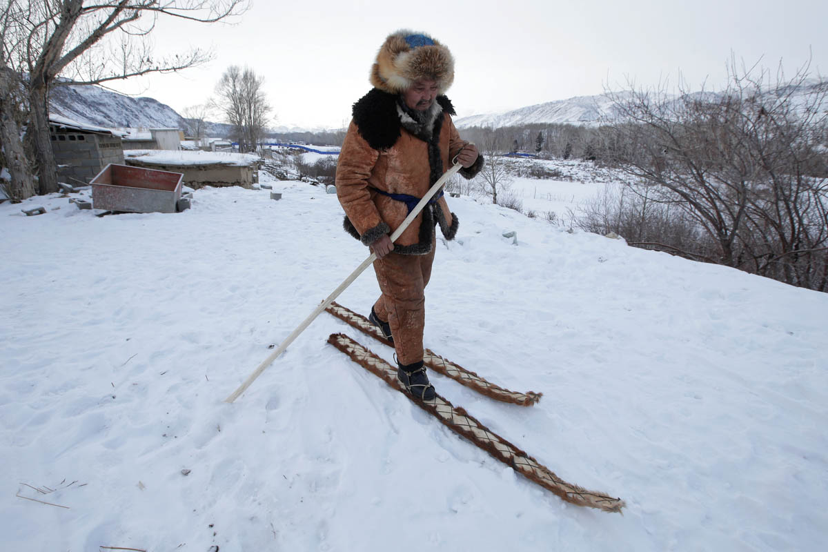 Local craftsman Slanbek, 63, tests traditional horsehide skis outside his house on the outskirts of Altay, in China's Xinjiang Autonomous Region. [Jason Lee/Reuters]