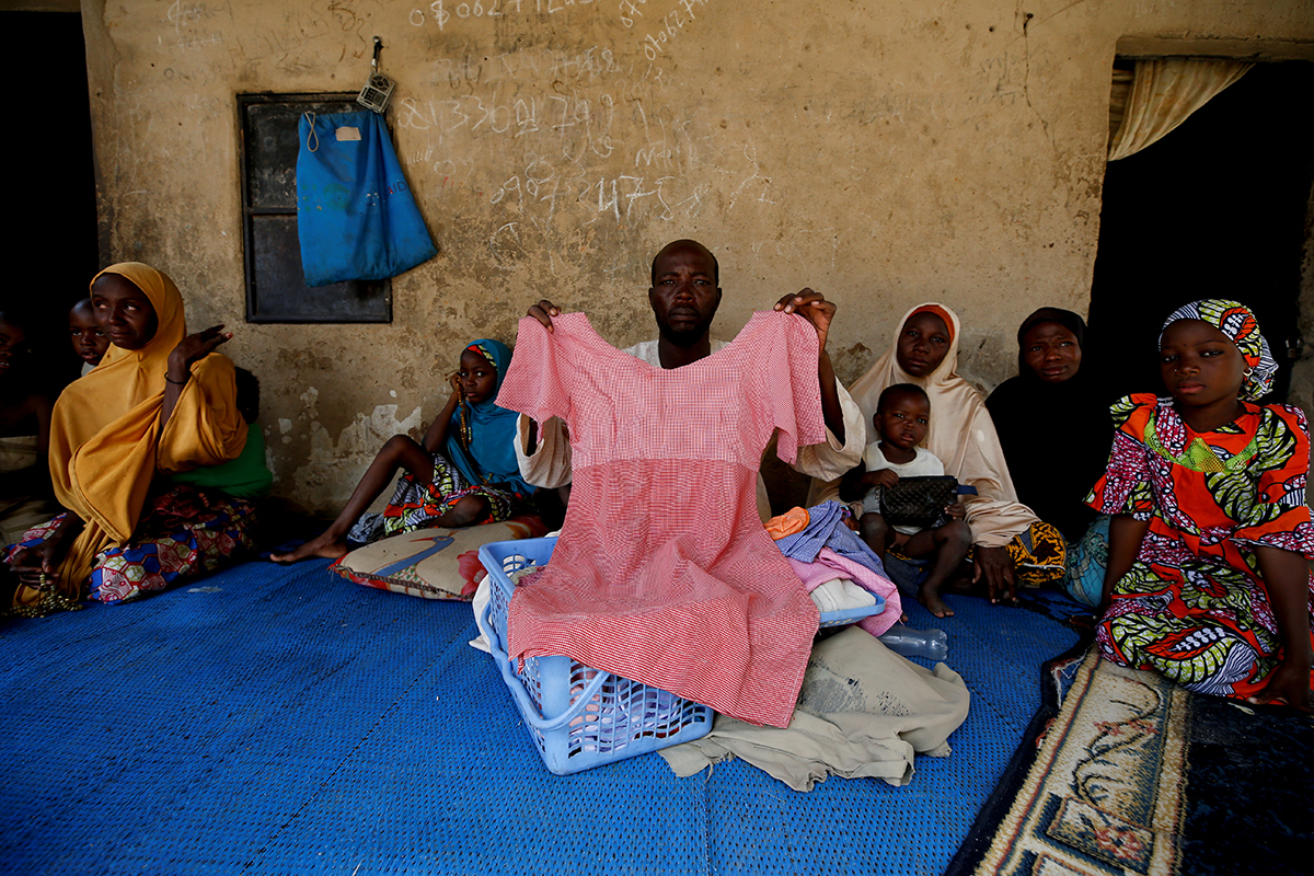 Kachalla Bukar, father of Aisha Kachalla, a missing student of Government Girls Science and Technical College, holds a dress of his daughter. [Afolabi Sotunde/Reuters]