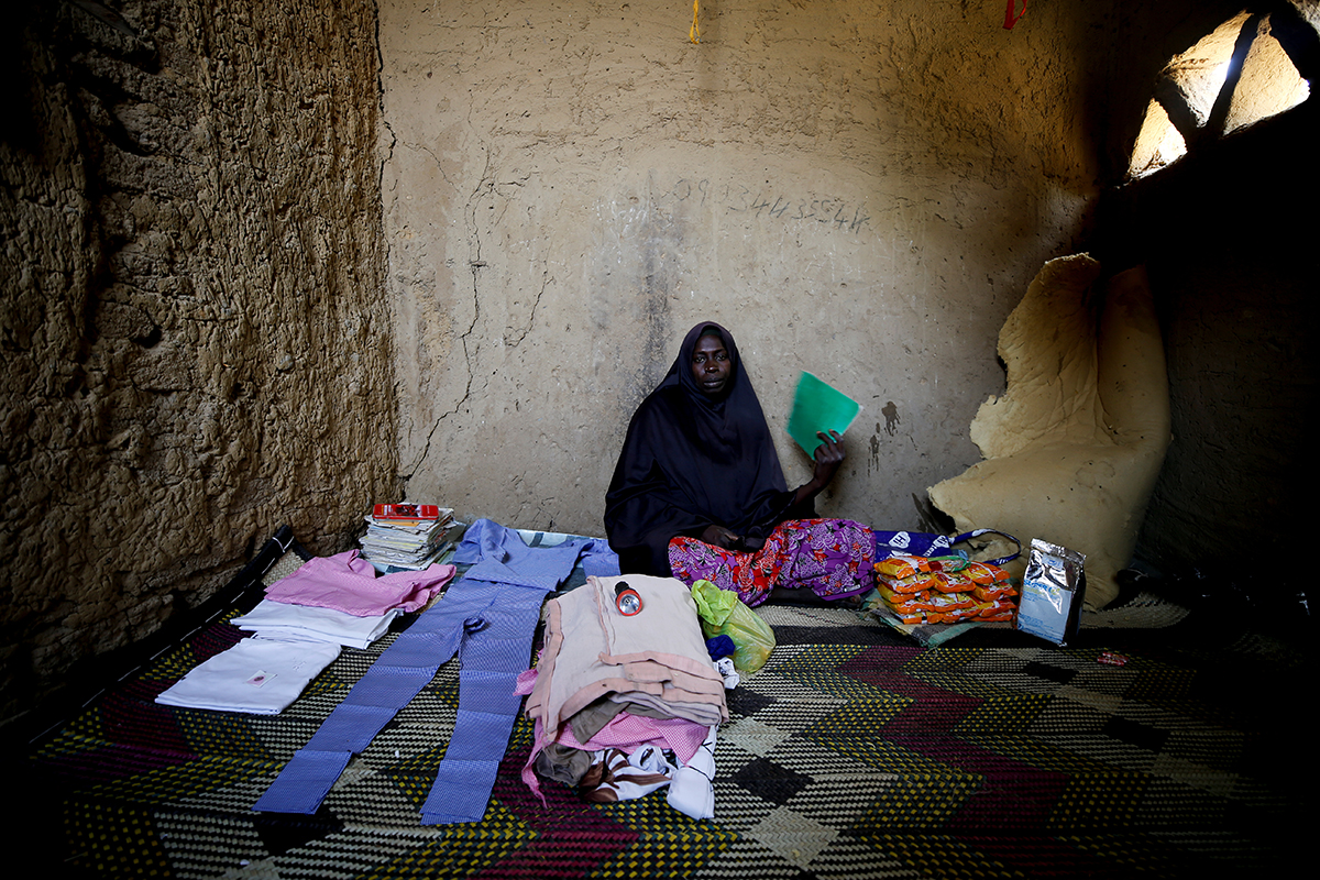 Hajiya Gana Mohammed, mother of Afisat Grah, a missing student, sits beside her daughter's books and clothes. [Afolabi Sotunde/Reuters]