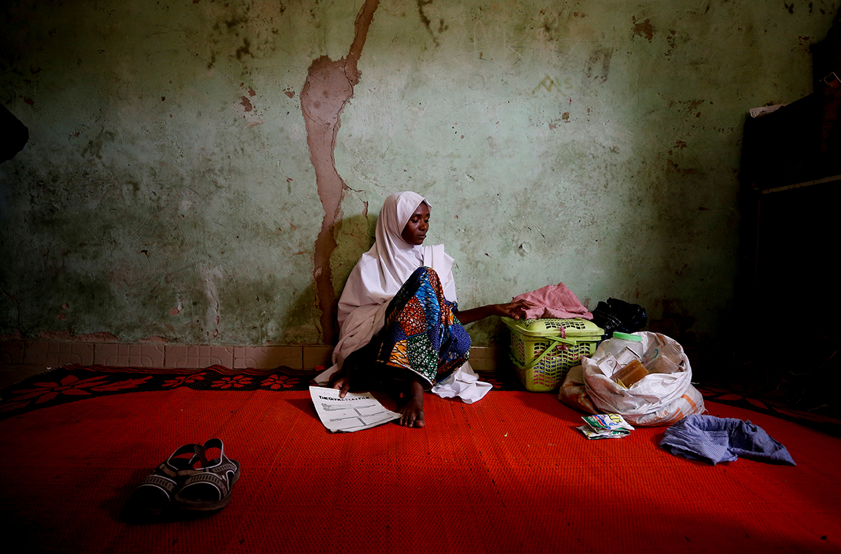 Adama Mustapha, mother of Salamutu, Fatima and Maryam Mustapha, missing students, sits near her daughters' clothing in her house. [Afolabi Sotunde/Reuters]