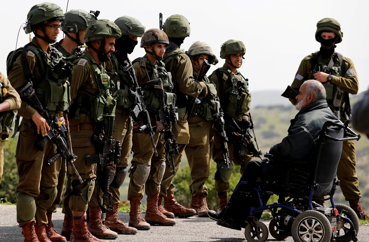 Israeli soldiers stand in front of a Palestinian in a wheelchair during a protest near Tubas, in the occupied West Bank. [Mohamad Torokman/Reuters]