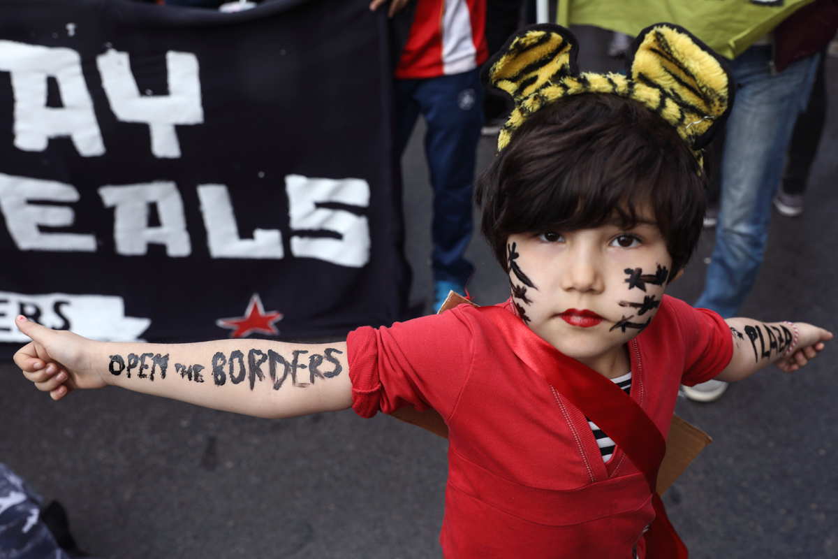 A girl poses for a photo during a rally in Athens, Greece, against the EU-Turkey deal to block the flow of refugees to Europe. [Yorgos Karahalis/AP Photo]