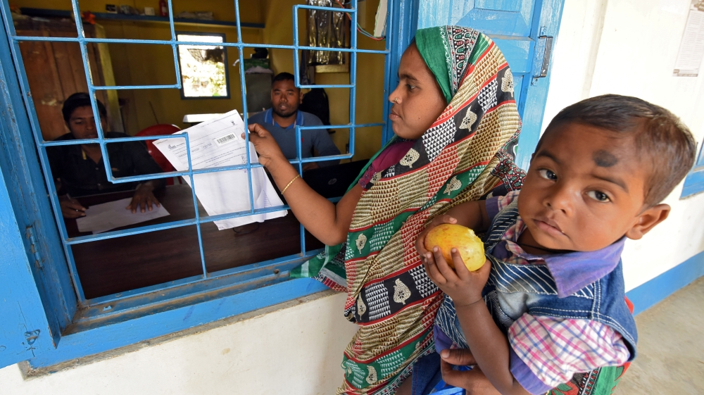 A woman carrying her son arrives to check her name on the draft list of the National Register of Citizens at an NRC centre in Chandamari village