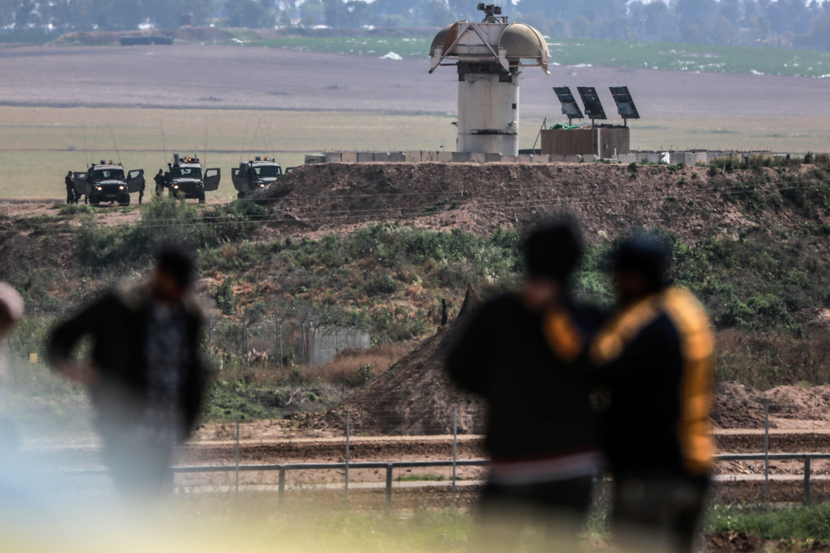Israeli soldiers and an army observation tower seen in the distance across from the Gaza border with Israel, east of Gaza City. [Hosam Salem/Al Jazeera]