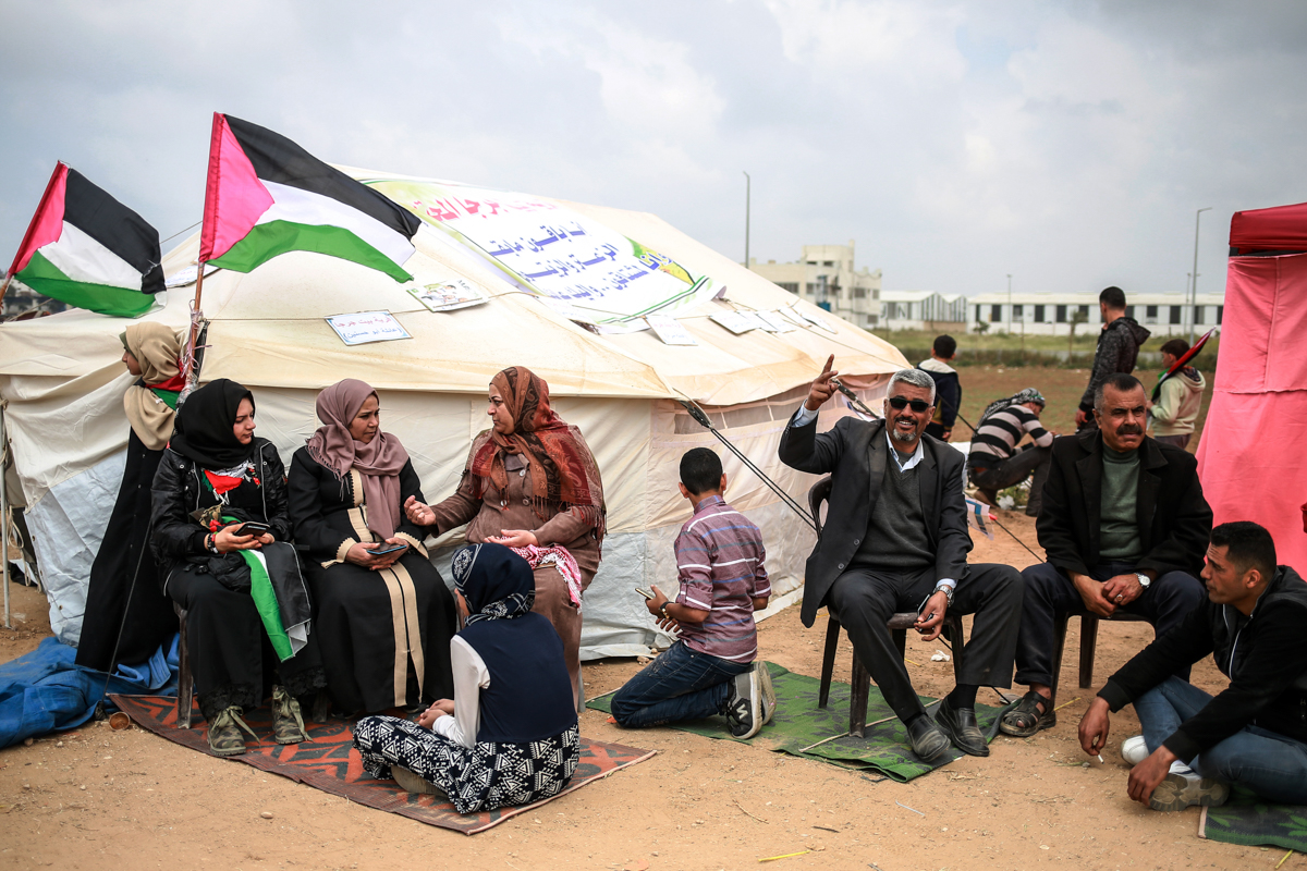 A family sits in front of their tent east of Gaza City. They have hung up signs of the names of their original villages to which they hope to return. [Hosam Salem/Al Jazeera]