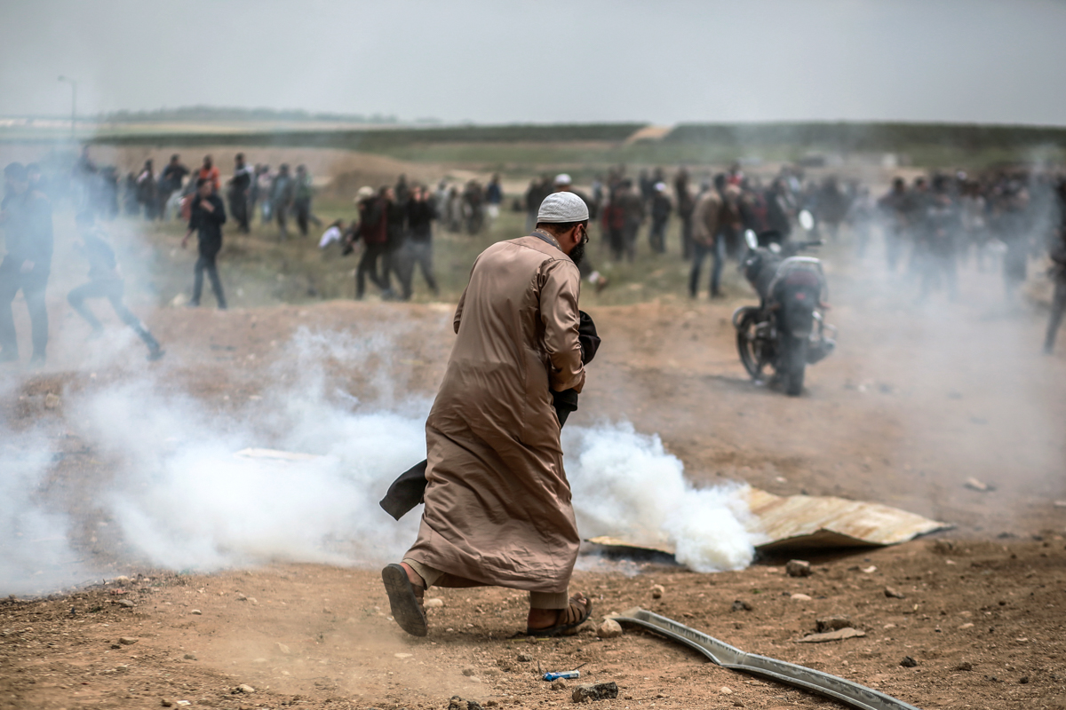 A man tries to put out the smoke from a tear gas canister fired by the Israeli army at Palestinian demonstrators. [Hosam Salem/Al Jazeera]