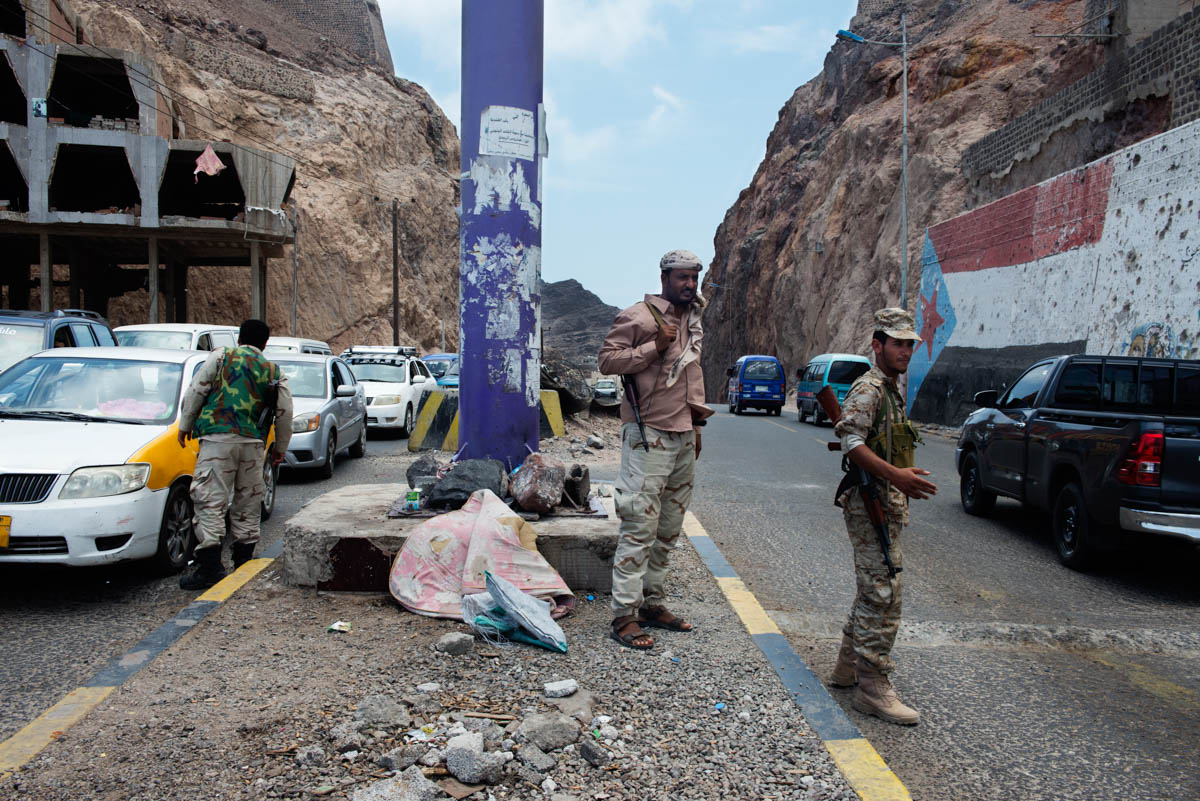 A checkpoint run by the Security Belt in Kraytar, a frequent target of al-Qaeda attacks in Aden. On the right is the flag of the former People's Democratic Republic of Yemen, symbolising the independence aspirations of the south. [Judith Prat/Al Jazeera]