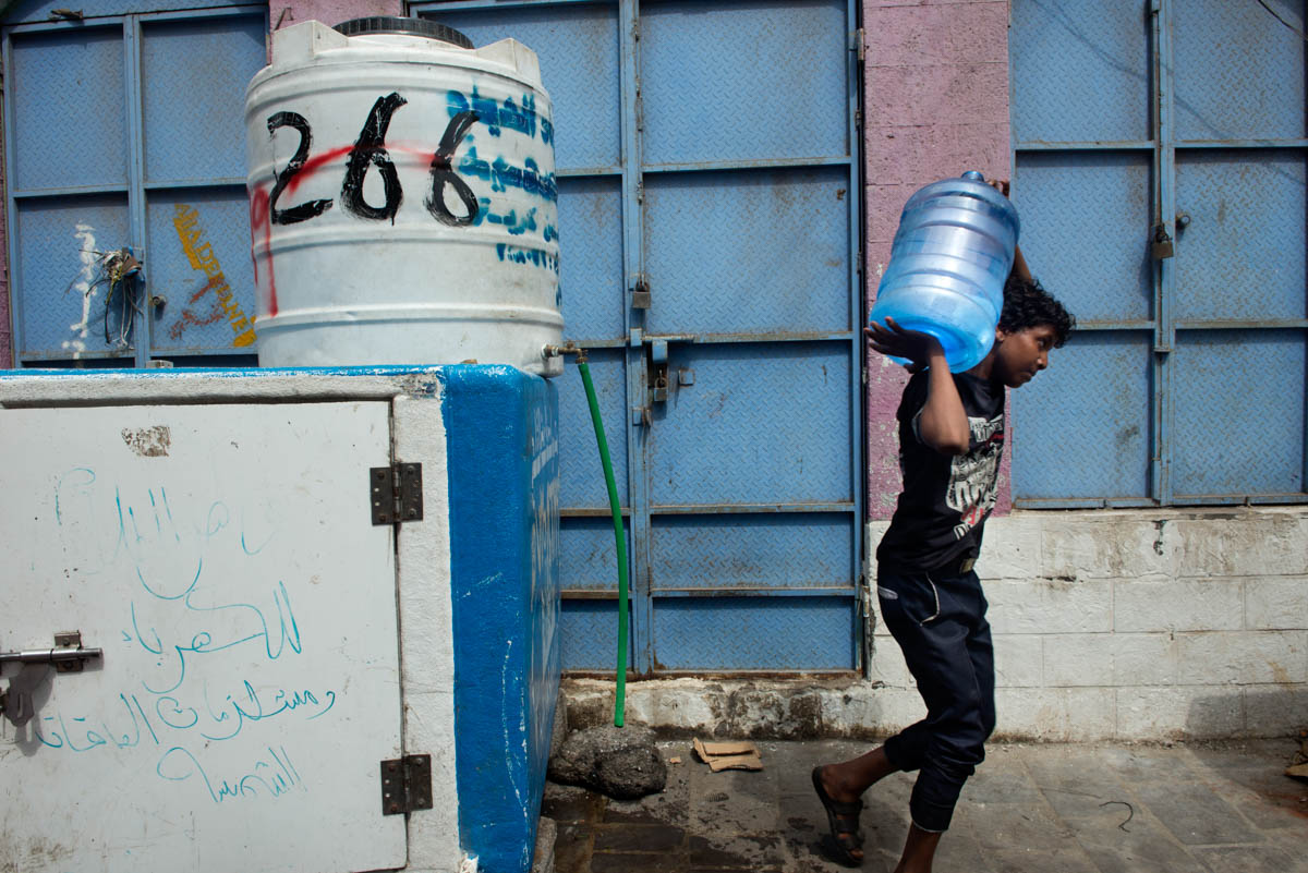 A boy carries drinking water in one of the existing points of sale and supply in Aden. [Judith Prat/Al Jazeera]
