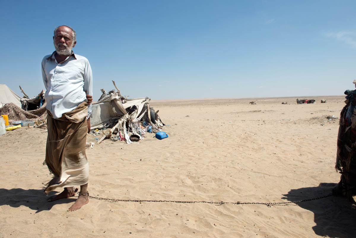 A man with psychological problems remains chained to his small tent in the Omran desert. Left to fend for themselves on the outskirts of Aden, the man and his family manage to survive despite being unable to purchase the medicines needed to treat his illness. [Judith Prat/Al Jazeera]