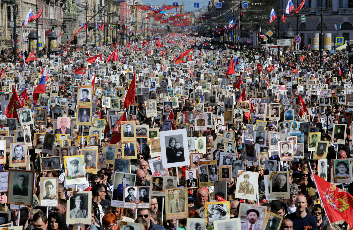 Local residents carry portraits of their ancestors, participants in World War II, as they celebrate the 73rd anniversary of the defeat of the Nazis in the second world war in St Petersburg, Russia. About one million people participated in the 'Immortal Regiment' march. [Dmitri Lovetsky/AP Photo]