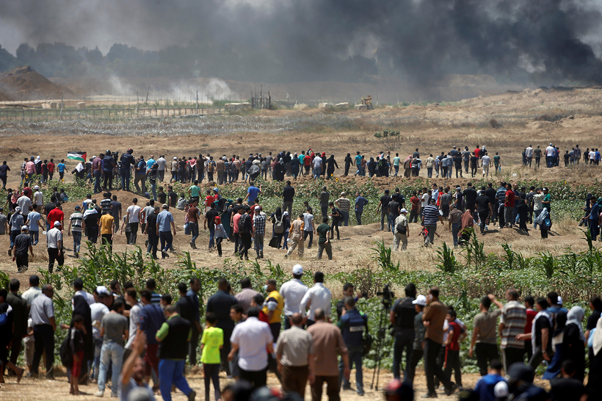 Palestinian demonstrators gather at the Israel-Gaza border east of Gaza City on Monday. [Mohammed Salem/Reuters]