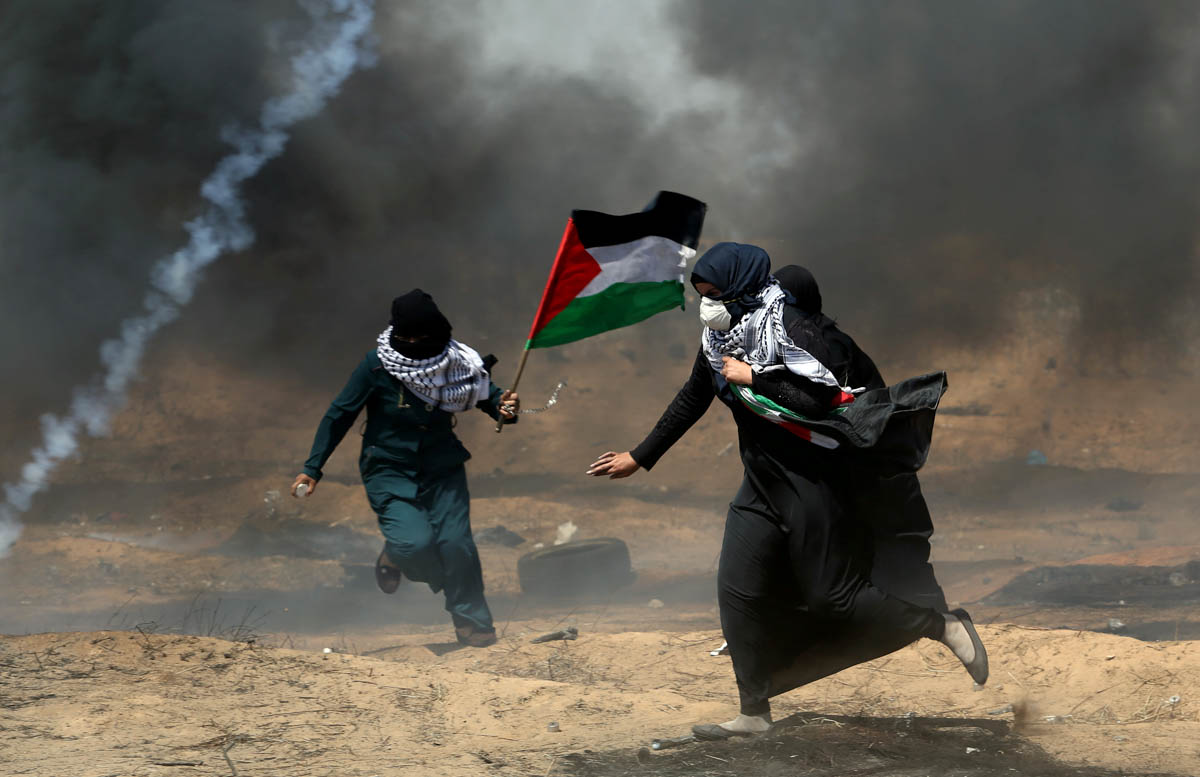 Female demonstrators run for cover from tear gas fired by Israeli forces during a protest where Palestinians demand the right to return to their homeland, at the Israel-Gaza border in the southern Gaza Strip. [Ibraheem Abu Mustafa/Reuters]