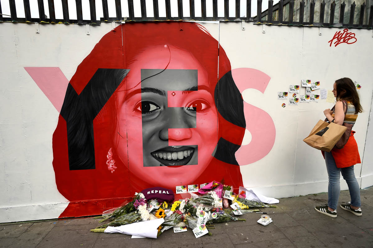 A woman looks at a new mural of Savita Halappanavar with flowers placed beneath it. The mural was put up on the day of the referendum on liberalising abortion laws in Dublin, Ireland. [Clodagh Kilcoyne/Reuters]