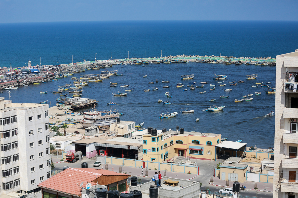 A general view of Gaza City's seaport as boats gather to set sail in support of the main vessel that intended to leave for Limassol, Cyprus. [Hosam Salem/Al Jazeera]