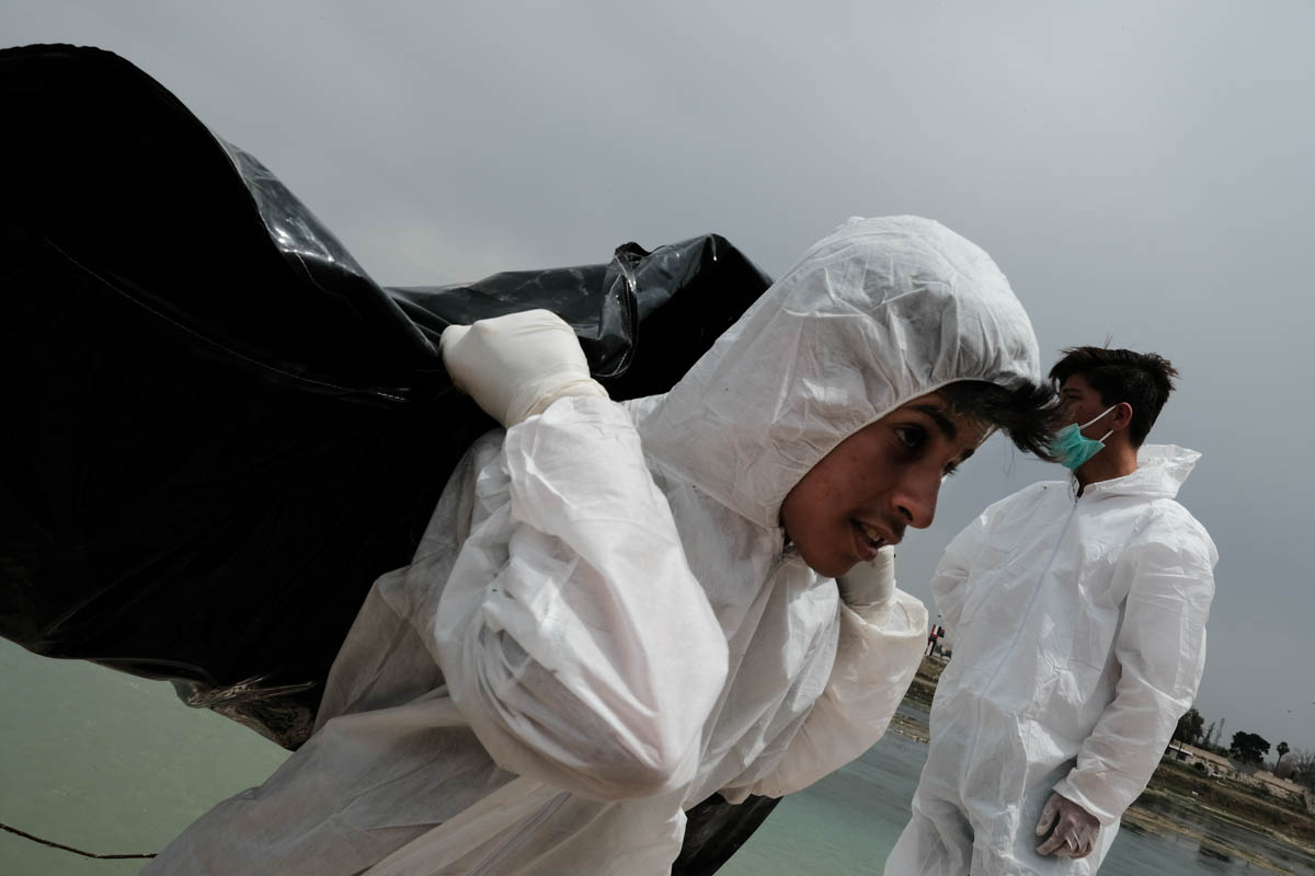 A volunteer collects a dead body. Many in the group are young, some just recently turned 18. [Vincent Haiges/Al Jazeera]