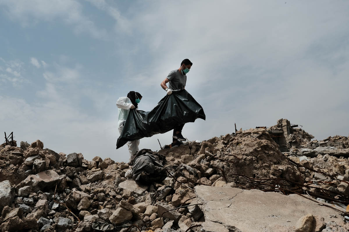 Volunteers carry a dead body across the rubble. The group works in the early morning hours due to the smell of the dead bodies. 'The bodies need to be removed. You can smell them in the neighbourhoods where people [have] already started to return,' says one volunteer. [Vincent Haiges/Al Jazeera]