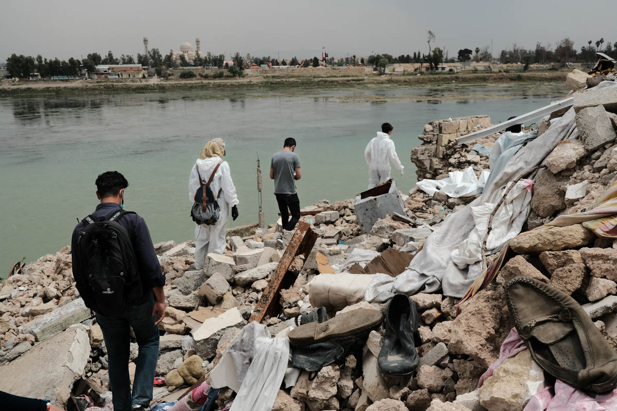 A part of the group walks through the debris of the al-Midan neighbourhood in Mosul's old town. They want to collect all the dead bodies - irrespective of their identity. [Vincent Haiges/Al Jazeera]