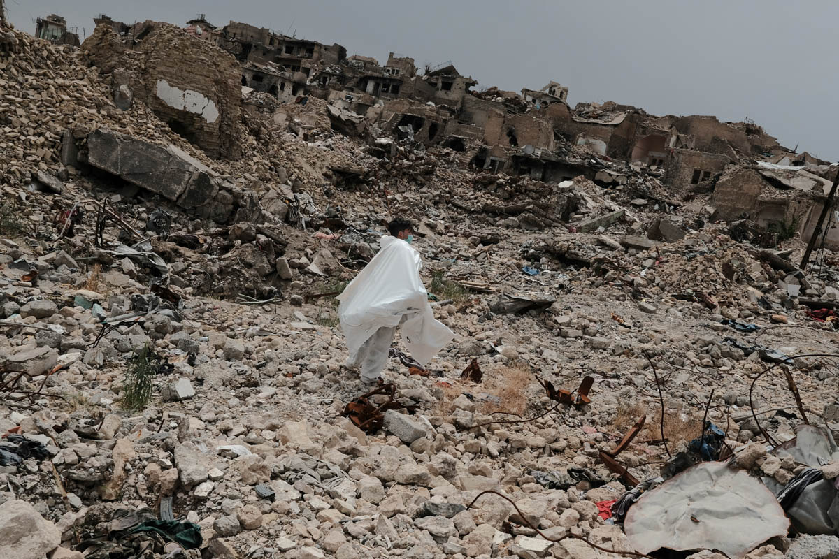 A volunteer carries a dead body through a completely destroyed part of the al-Midan neighbourhood. [Vincent Haiges/Al Jazeera]